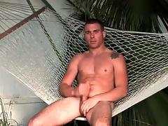 Hot guy sits in a hammock and masturbates